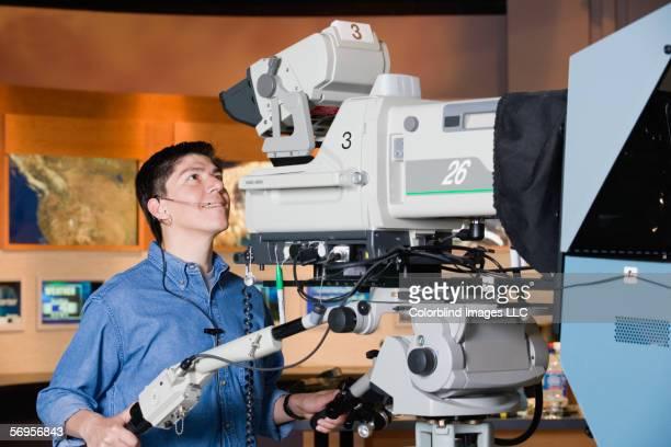 Camera man running camera in newsroom