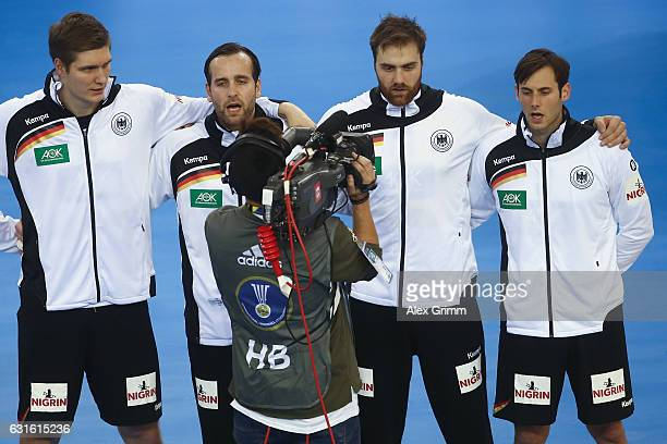 TV camera man walks past Finn Lemke Silvio Heinevetter Andreas Wolff and Uwe Gensheimer of the German team during the national anthem prior to the...