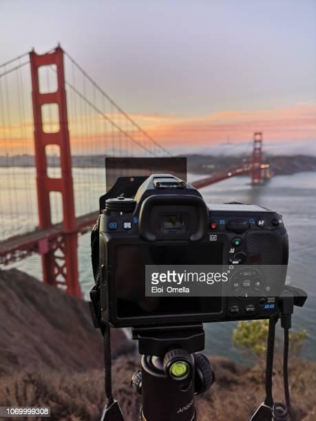 cámara en trípode delante de puente de golden gate tomar foto. san francisco. ca - san francisco california fotografías e imágenes de stock