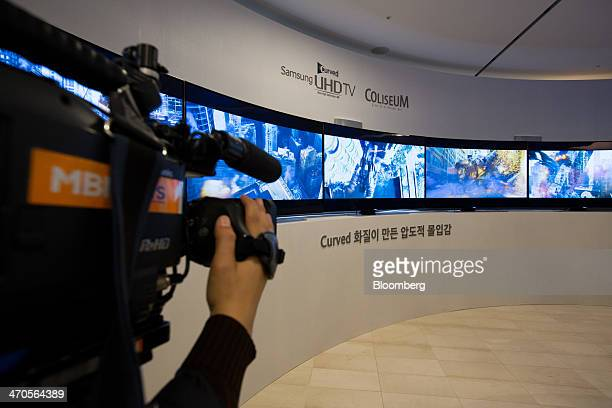 A camera operator shoots Samsung Electronics Co curved Ultra High Definition televisions displayed at a media event in Seoul South Korea on Thursday...