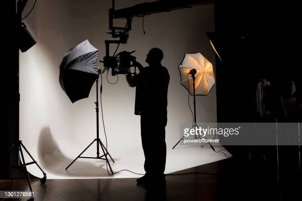 camera operator working behind the scenes while filming on a film set - film set stock pictures, royalty-free photos & images