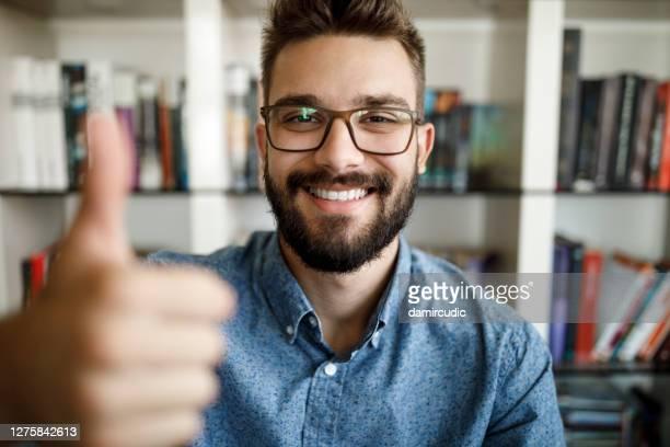 het standpunt van de camera van jonge mens die duimen omhoog bij huisbureau houdt - extatisch stockfoto's en -beelden