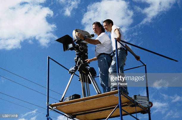 Cameraman and assistant on scaffolding with camera, low angle view