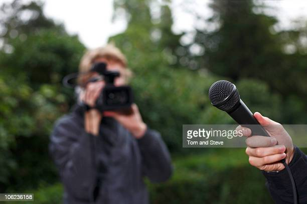 cameraman and microphone for filmed interview - film crew stock pictures, royalty-free photos & images