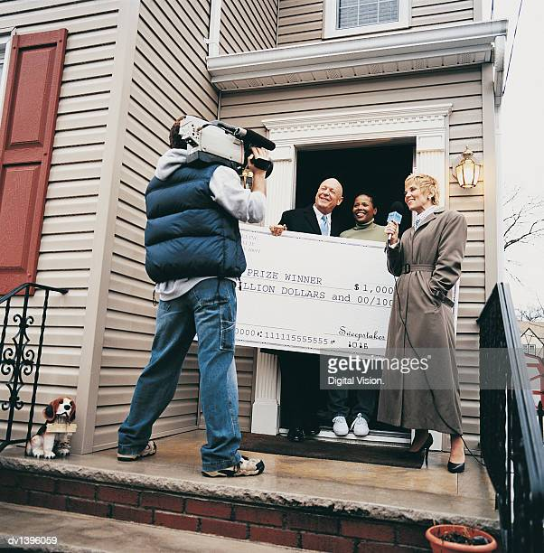 cameraman and tv presenter interviewing a couple holding a large winning cheque - big mike stock pictures, royalty-free photos & images
