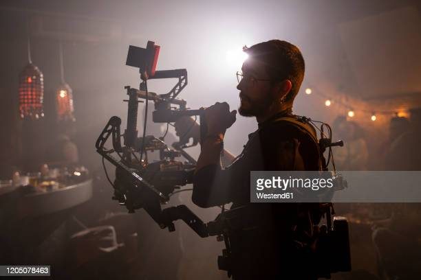 cameraman at work on movie set - cinematographer stock pictures, royalty-free photos & images