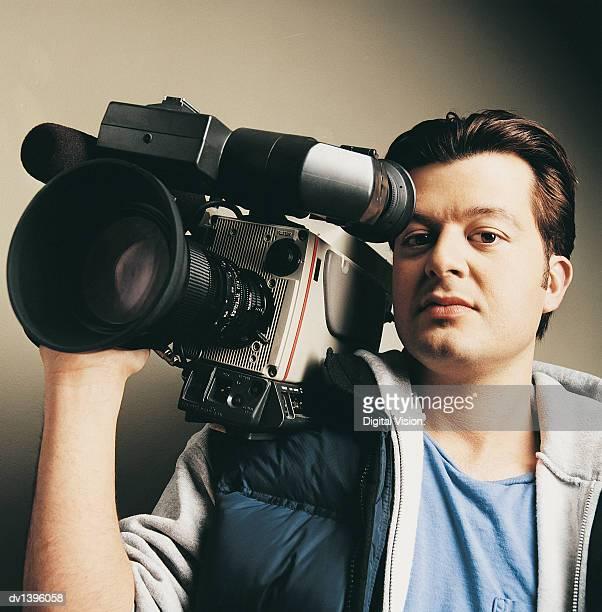 TV Cameraman Carrying a Camera