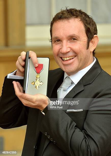 BBC cameraman Darren Conway holds his OBE after it was presented to him by Prince Charles Prince of Wales during an Investiture Ceremony at...