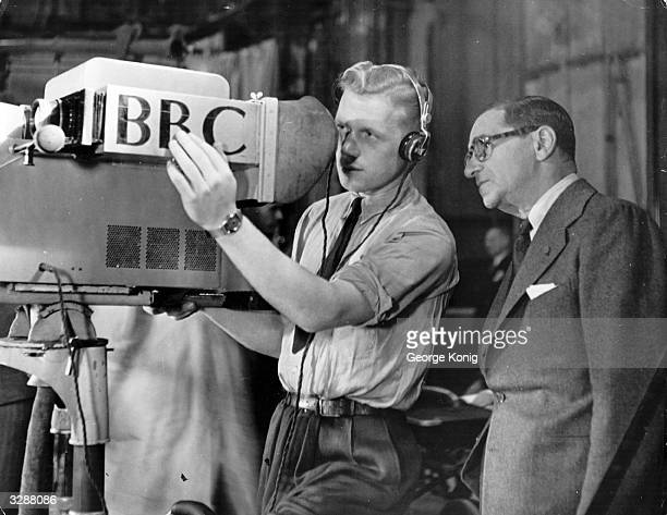 Cameraman explains the technicalities of the television camera to Russian-born US composer Irving Berlin , before the broadcasting of a programme...