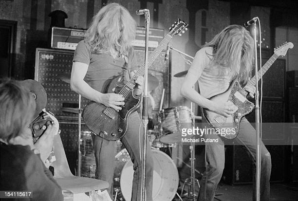 A cameraman filming guitarists Rick Parfitt and Francis Rossi during a performance with English rock group Status Quo at the Marquee Club London 21st...