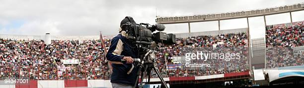 cameraman filming in full soccer stadium - television camera stock pictures, royalty-free photos & images