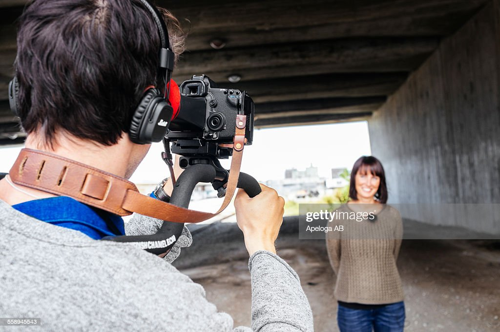 Cameraman filming news reporter under bridge : Stock Photo