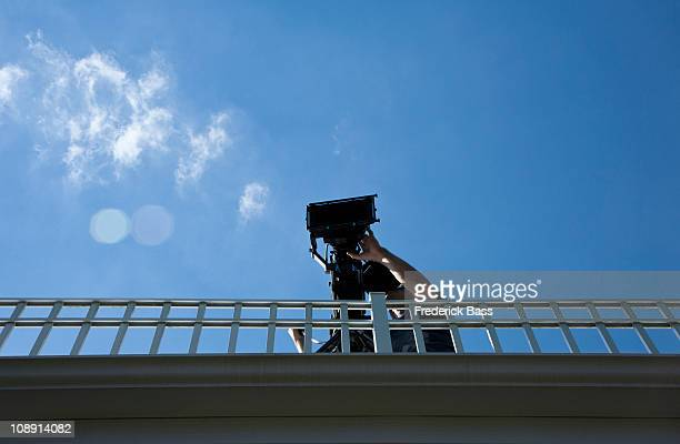A cameraman filming on a pedestrian bridge, low angle view