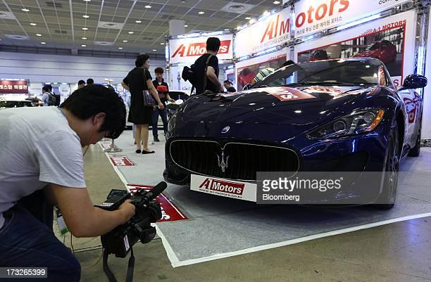 A cameraman films a Fiat SpA Maserati GranTurismo vehicle at the Seoul Auto Salon 2013 in Seoul South Korea on Thursday July 11 2013 The Seoul Auto...