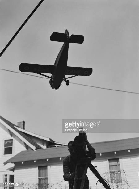 Cameraman films a miniature Travel Air 6000, aka the Curtiss-Wright 6B, for an aerial scene in a movie, circa 1939. The shot may be for the Laurel...
