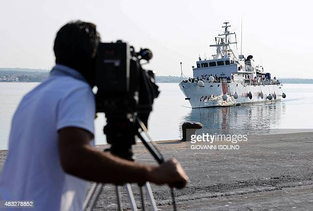 A cameraman films as the patrol vessel Fiorillo of the Italian Coast Guard arrives in the port of Pozzallo on August 7 2015 after saving some 387...