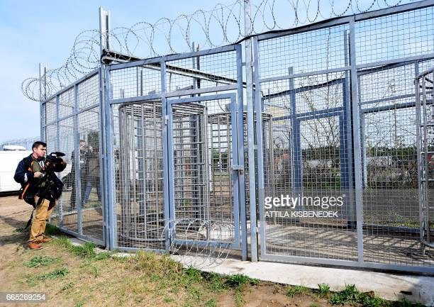 A cameraman films at the migrants' entrance of the Tompa border station transit zone on April 6 2017 as the Hungarian Interior Minister Sandor Pinter...