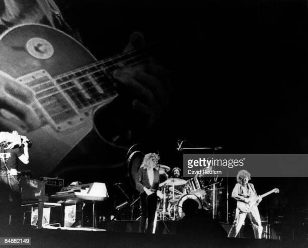 Cameraman films, from left, Robert Plant, John Bonham and Jimmy Page of English rock group Led Zeppelin performing live on stage with a background...