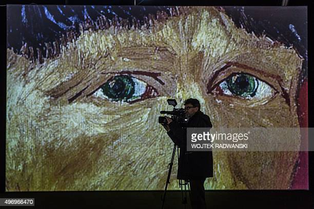 A cameraman films in front of a screen displaying part of a painting by Dutch artist Vincent Van Gogh during the official opening of the 'Van Gogh...