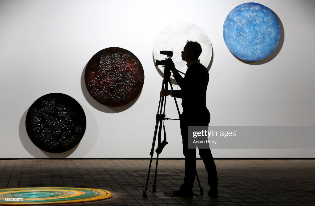 A cameraman films in front of the sculptures by Kholoud Mohammed Al Musfer (from L to R), 'Dark Side of the Moon,' 'Blood Moon II,' 'Moon Glow,' and 'Blue Moon,' prior to the opening of the 'Art From Qatar' exhibition at Kraftwerk Berlin on December 8, 2017 in Berlin, Germany. The exhibition, in a former East German power plant, will feature 294 works from 73 artists. It opens on December 9 and runs until January 3.
