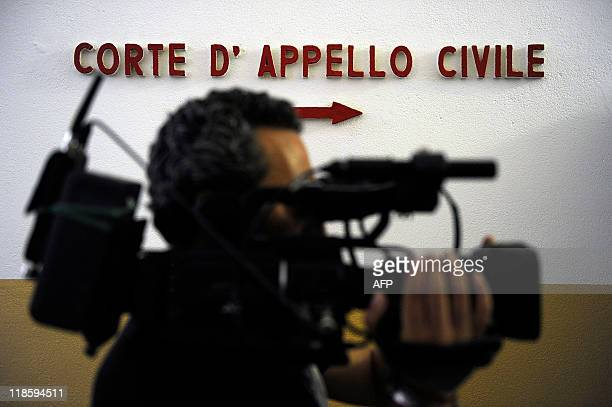 A cameraman films inside the Milan court house on July 9 2011 A Milan court ordered Italian premier Silvio Berlusconi's Fininvest company today to...