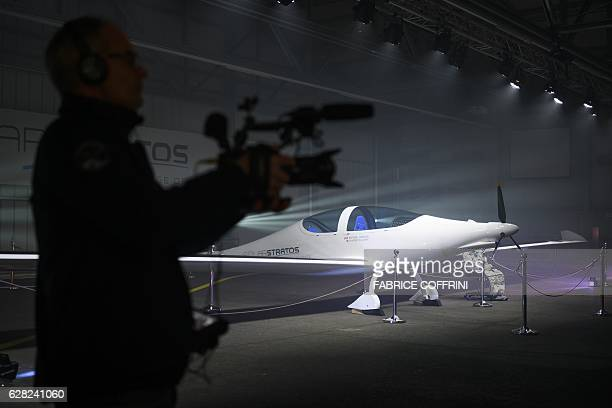 A cameraman films next to the SolarStratos stratospheric powered aircraft after its rollout on December 7 2016 in Payerne Switzerland Swiss...