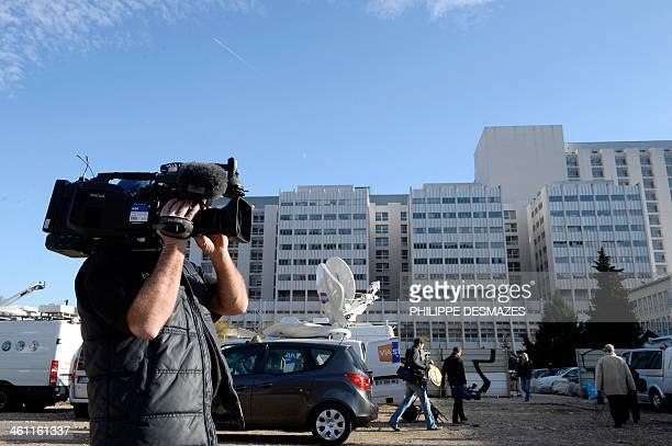 A cameraman films on January 7 2014 in front of the Grenoble University Hospital Centre in the French Alps where retired seventime German Formula One...