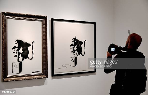 A cameraman films on May 23 a painting entitled 'Monkey detonator ' by Englandbased graffiti artist Banksy during the 'Guerra Capitalismo Liberta'...