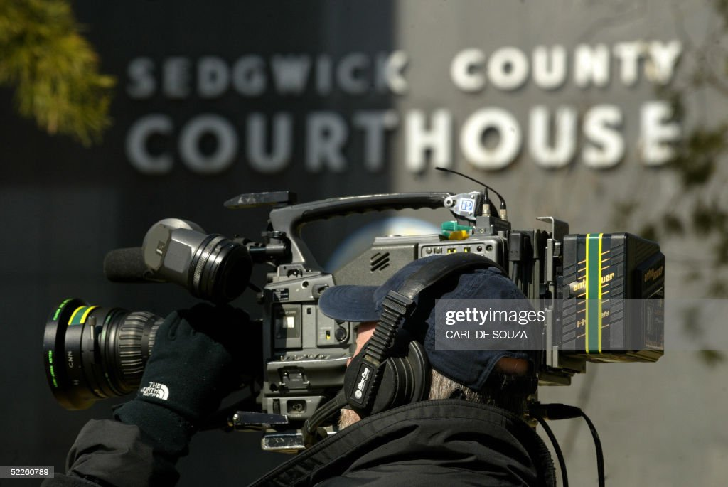 A cameraman films outside Sedgwick County Court house during a press briefing after Dennis L Rader's arraignment for 10 counts of first degree murder in Wichita, Kansas, 01 March 2005. Rader, a 59-year-old former security company worker accused of being the notorious 'BTK' serial killer was charged with 10 counts of murder in connection with a case which baffled Kansas police for three decades. Bail was put at 10 million dollars and his next court appearance set for March 15. Rader made his first court appearance via video link since he was arrested 25 February on suspicion of being the killer known as BTK, which stand for 'Bind, Torture, Kill' the grisly method employed by the murderer who terrorized the Wichita area for years. Authorities reopened their investigation in March 2004 after the killer, who had remained silent for decades, wrote to a local television station and sent a package containing the driver's license of a 25-year-old woman killed in December 1977. A Cub Scout leader, devout churchgoer and married father of two, Rader was a respected member of the local community before his arrest. AFP PHOTO/Carl DE