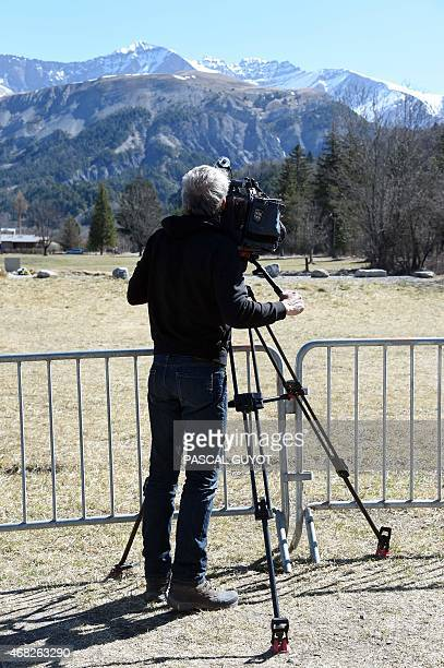 A cameraman films the mountains where the site of the Germanwings Airbus A320 crash is located in the small village of Le Vernet French Alps on April...
