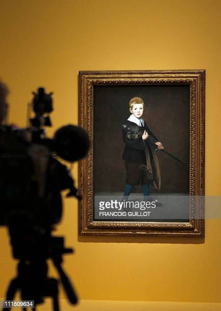 A cameraman films the painting 'L'enfant à l'epee' made in 1868 by French impressionist artist Edouard Manet during the press visit of the...