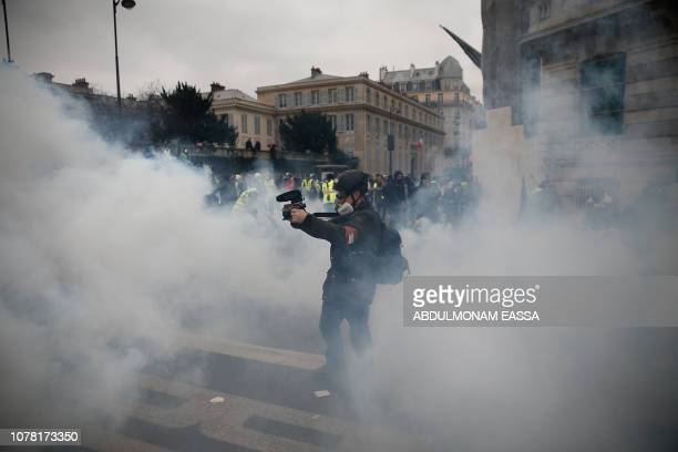A cameraman films through a cloud of teargas in Paris on January 5 during an antigovernment demonstration called by the yellow vest 'Gilets Jaunes'...