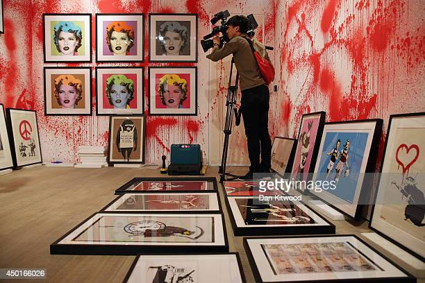Cameraman films work during a press preview of the first unauthorized retrospective of works by UK artist Banksy on June 6, 2014 in London, England....