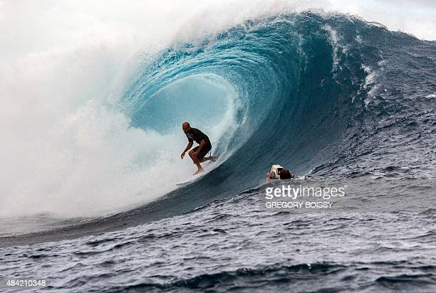 A cameraman floats in the water filming USA's Kelly Slater as he competes in the 2015 Billabong Pro Tahiti World Surf league tour no7 along the...