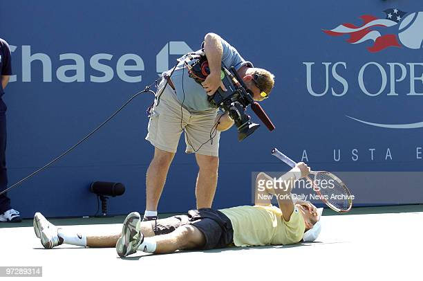 Cameraman gets close to the action as Jarkko Nieminen of Finland falls to the court and celebrates his win over Fernando Verdasco of Spain during...
