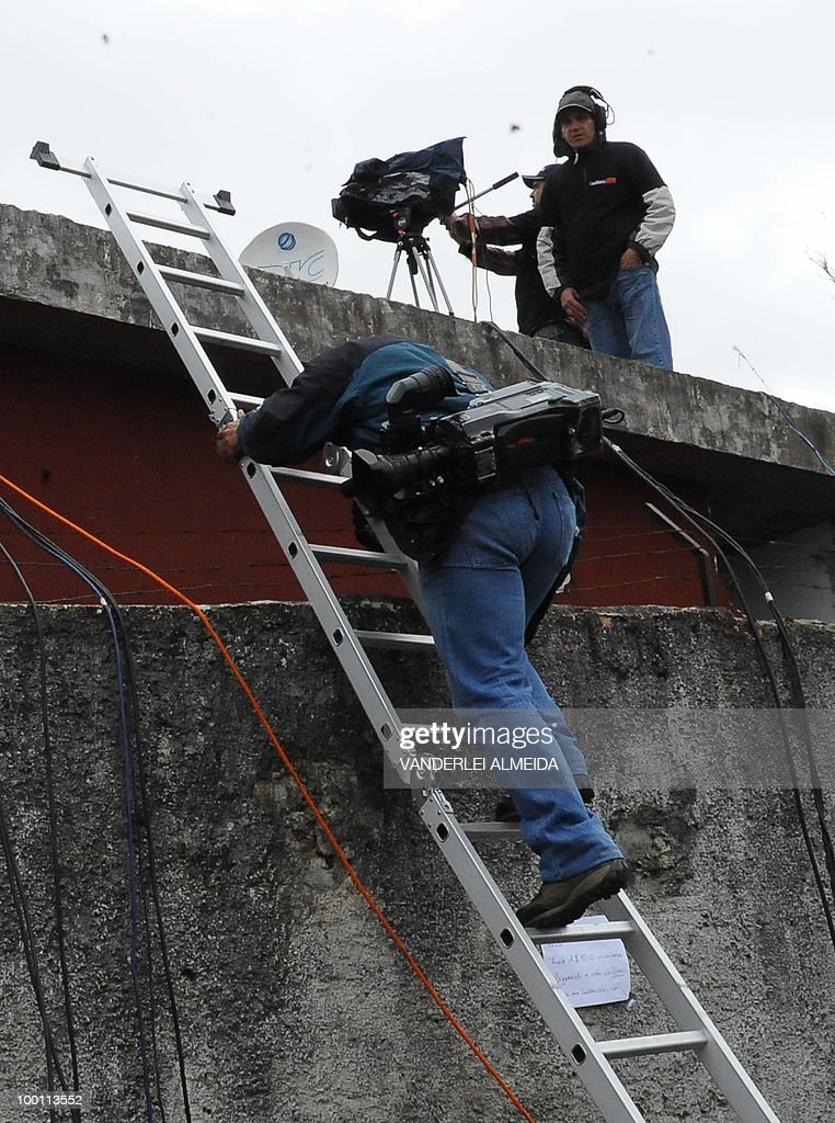 A TV cameraman gets on a roof to look inside of the training center where the Brazilian football team gets prepared for the FIFA World Cup South Africa-2010, in Curitiva on May 21, 2010.
