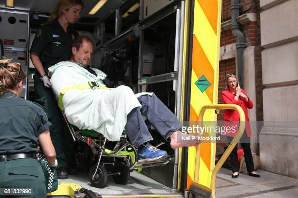 Cameraman Giles Wooltorton is helped by Ambulance staff after reportedly being hit by Labour Leader Jeremy Corbyn's vehicle outside Savoy Place, as...
