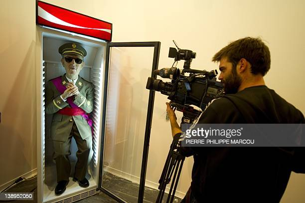 A cameraman grabs pictures of a sculpture by artist Eugenio Moreno representing Spanish dictator Francisco Franco on a soda vending machine displayed...