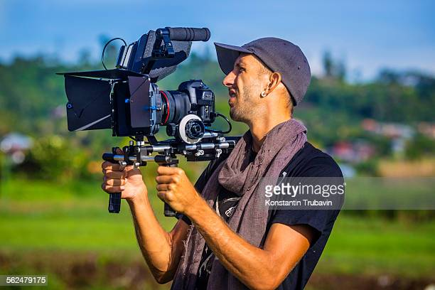 a cameraman holding camera in bali,indonesia. - cinematographer stock pictures, royalty-free photos & images