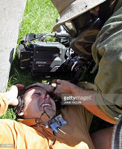 Cameraman is helped by another journalist after being injured during clashes in a protest against the APEC Forum, 19 November 2004 in Santiago....