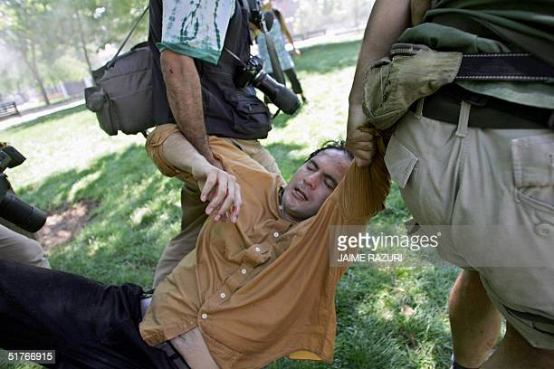 Cameraman is helped by other journalists after been injured during clashes in Santiago against the APEC Forum, 19 November 2004. Chilean riot squads...