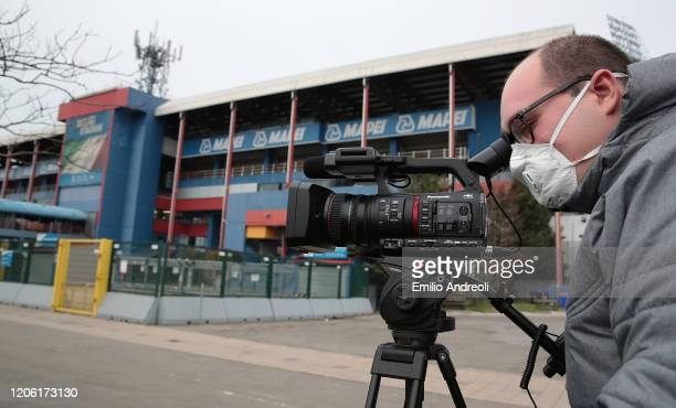 A cameraman is seen with the protective mask outside the empty stadium fans cannot attend the match due to the medical emergency Covid19 prior to the...