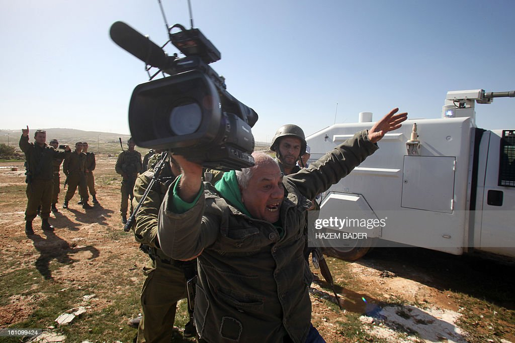 A cameraman of Associated Press (AP) news agency is arrested by an Israeli soldier as Palestinian activists tried to set up a new encampment to protest against settlement building in the Yatta, south of the West Bank city of Hebron on February 9, 2013. Soldiers dismantled tents that were being erected in two different areas near the town of Yatta, and forced activists to leave, the Palestinian witnesses said. BADER