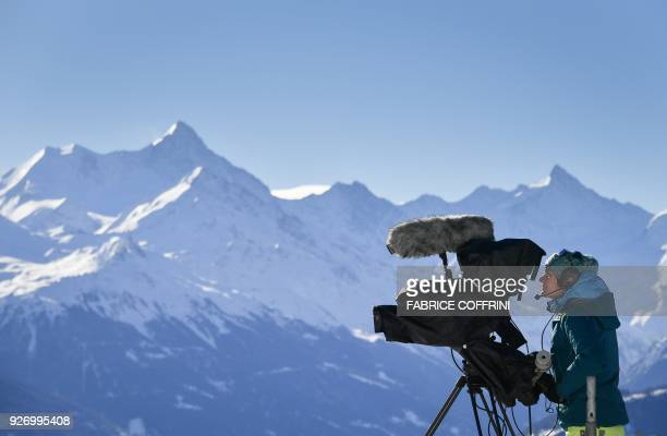 A cameraman of Swiss Broadcasting Corporation operates with the Swiss Alps in the background during a ski race in CransMontana on March 4 2018 Swiss...