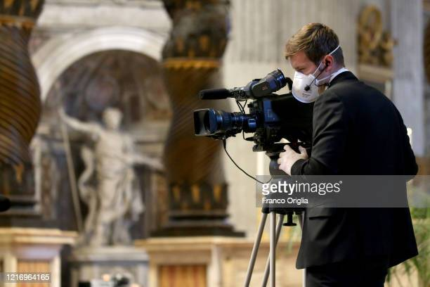 A cameraman of the Vatican TV wearing a protective mask attends Pope Francis' Palm Sunday Mass in an empty Vatican Basilica of St Peter's due to the...