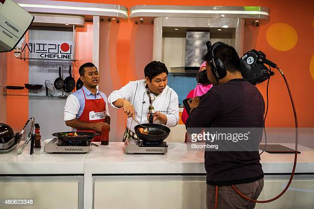 A cameraman operates a broadcast video camera during the recording of a cooking segment on the television show 'Go Shop' for Astro Malaysia Holdings...