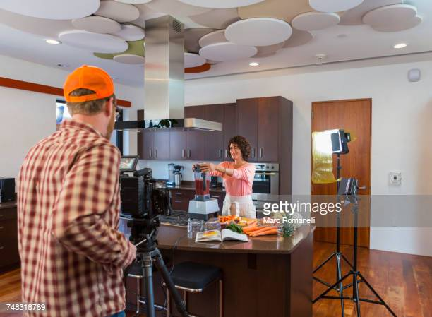 cameraman recording woman preparing smoothie in domestic kitchen - 放送 ストックフォトと画像