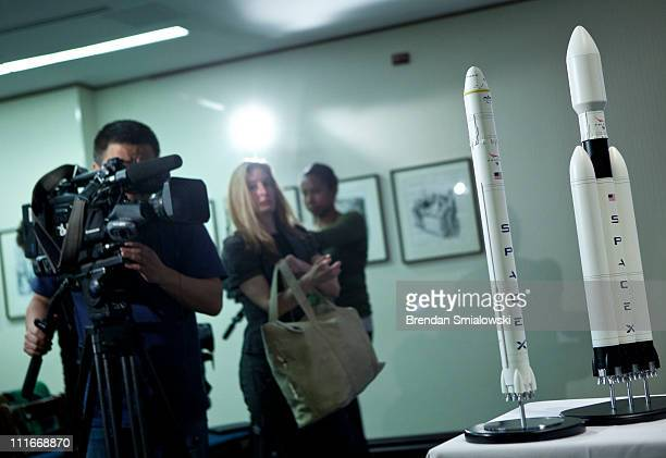 TV cameraman records a model of SpaceX's Falcon Heavy rocket after a news conference at the National Press Club April 5 2011 in Washington DC Elon...