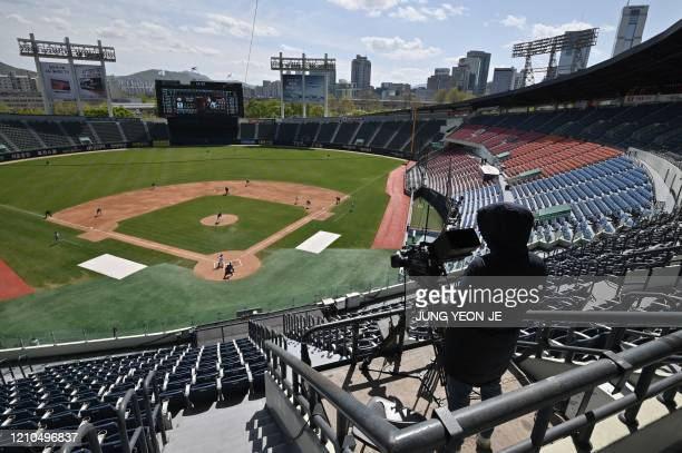 Cameraman records footage among empty stands during a pre-season baseball game between Seoul-based Doosan Bears and LG Twins at Jamsil stadium in...