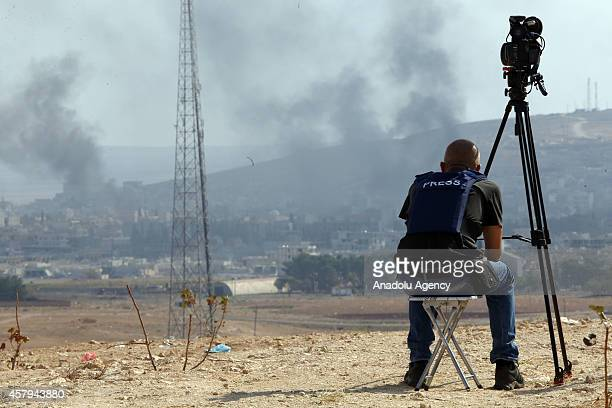 A cameraman records smoke rising from Kobani town of northern Syria during the intensified clashes between Islamic State of Iraq and Levant members...